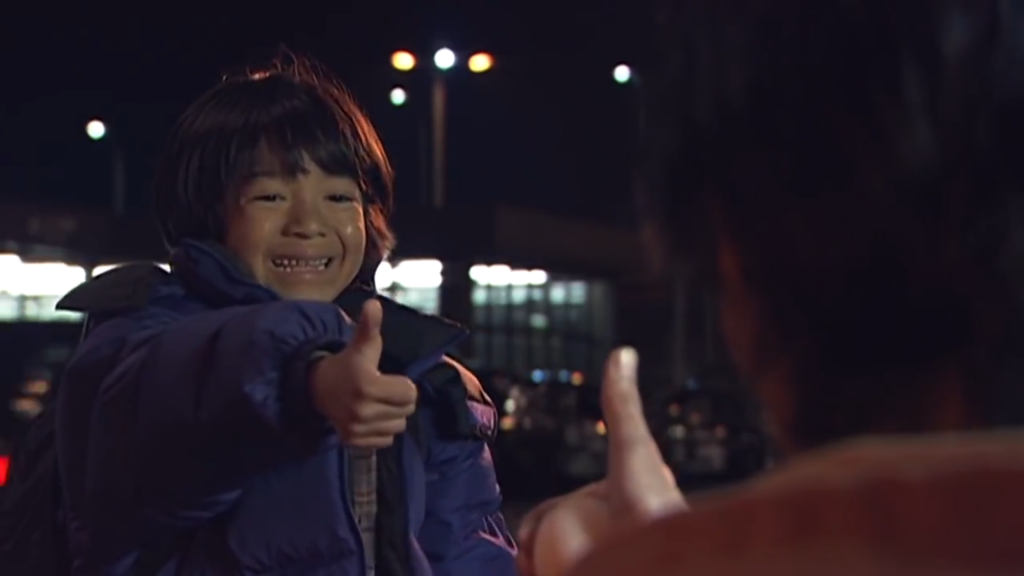 A child is smiling through tears and giving a thumbs up. We also see the back of an adult Godai Yusuke, giving a thumbs up back.